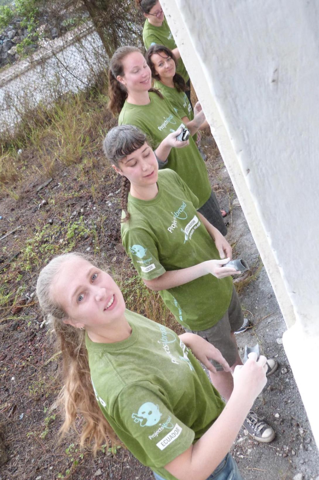 Ecuador volunteer group painting a wall